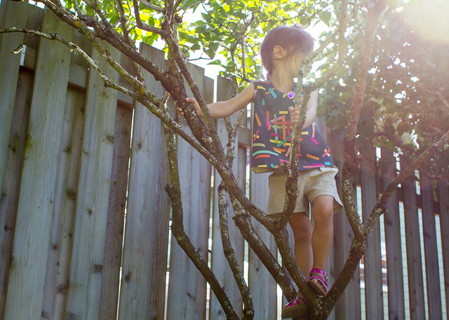 climbing a tree in her finch top and shorts