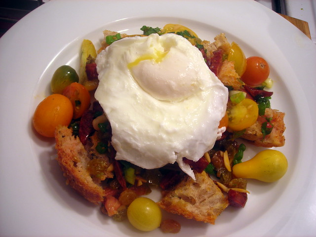 Tomato and crispy sourdough bread salad, with Spanish chorizo, almonds and a poached farm egg