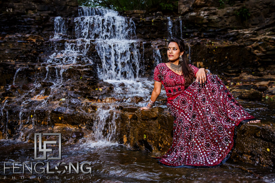 Indian bride poses in front of a waterfall