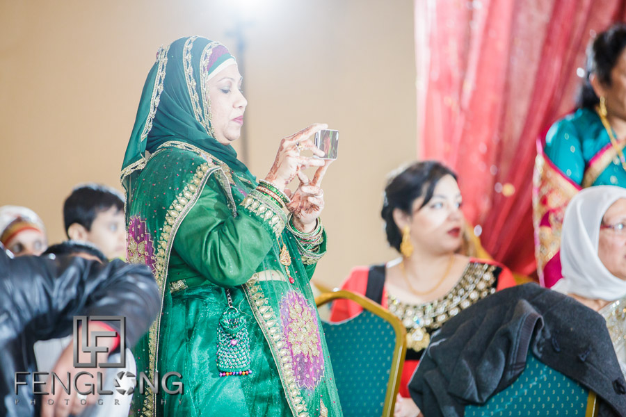 Guest taking photo with iPhone during wedding