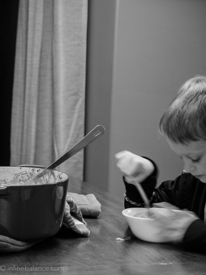 black & white photo, boy eating cauliflower mac and cheese