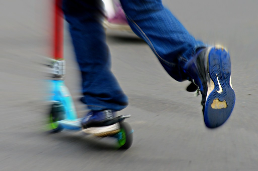 Photo of kid on scooter showing his legs only.  The bottom sole of his shoe has a Nike Logo on it and the sole of the shoe is well worn.