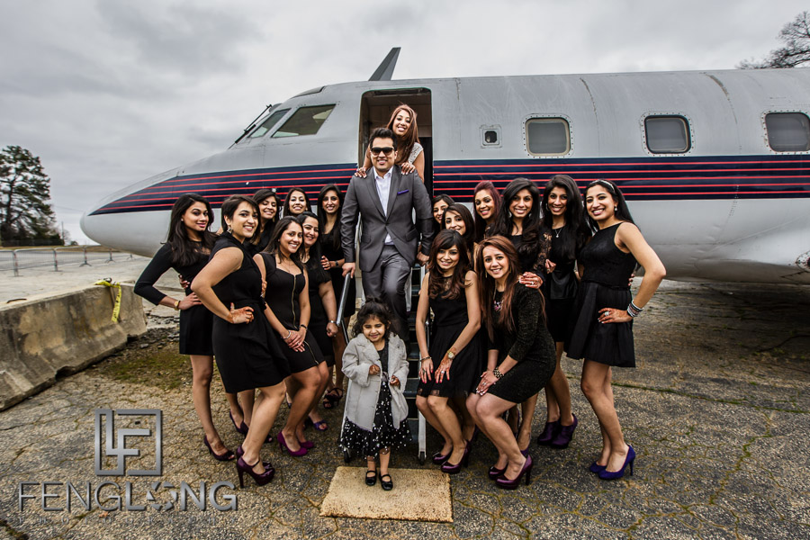 Ismaili Indian bride and groom with bridesmaids in front of airplane for pre-wedding photos