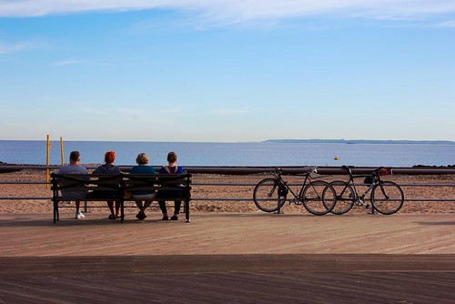 Four people and two bikes by the beach by laura shimili