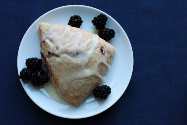 Top-down view of a big scone on a white plate topped with a glaze and surrounded by blackberries.