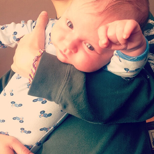 A baby in his mama's arms with one of his little pudgy arms extended.