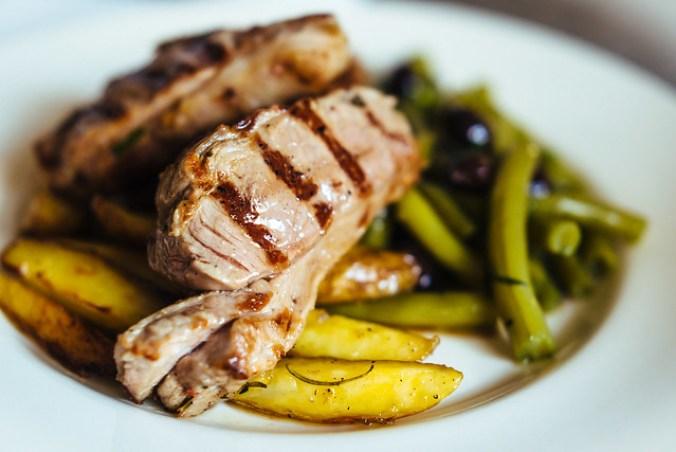 Kort gegrilde lamskoteletjes met daarbij sperziebonen in knoflookboter met bonenkruid en zwarte olijven - veel smaak in weinig tijd.