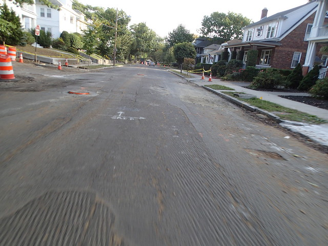 River Avenue with grooved surface, potholes and raised structures
