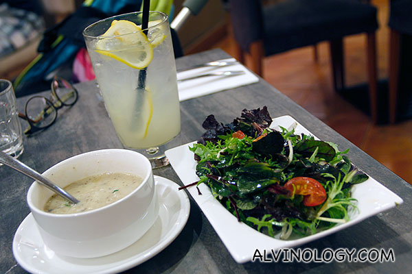 Salad, drink and soup that comes with a set meal