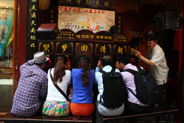 Tourists watching a mini show through small holes