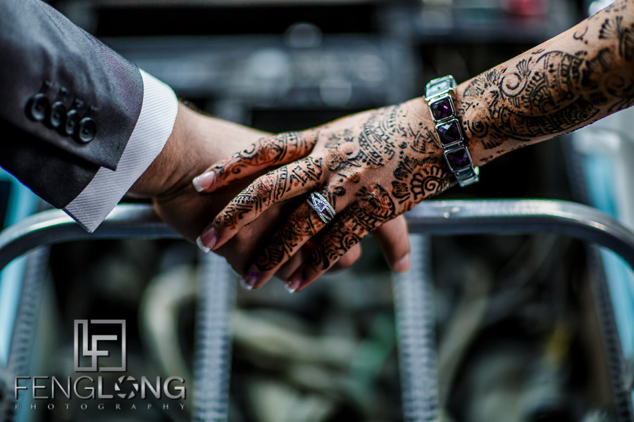 Bride and groom holding hands in cockpit showing rings and henna