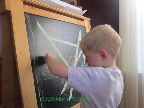 boy peeling masking tape off a chalkboard easle