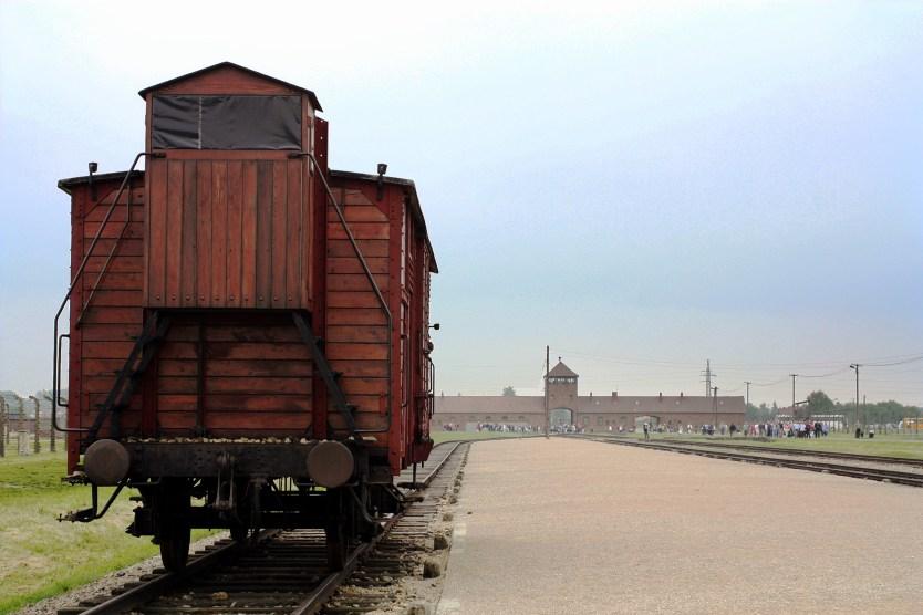 Train car with the main gate in the background, Birkenau (Auschwitz II).