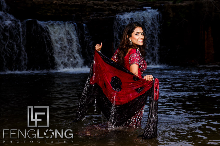 Indian bride in the water in romantic pose wearing a saree