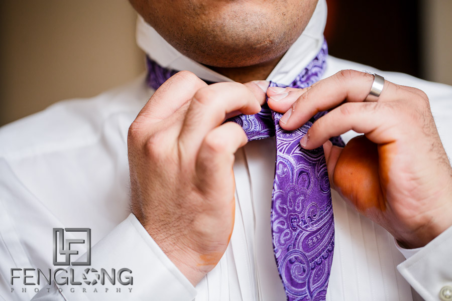 Groom tying a bowtie for his wedding reception
