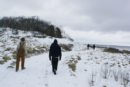 Friends walk through the snowy dunes