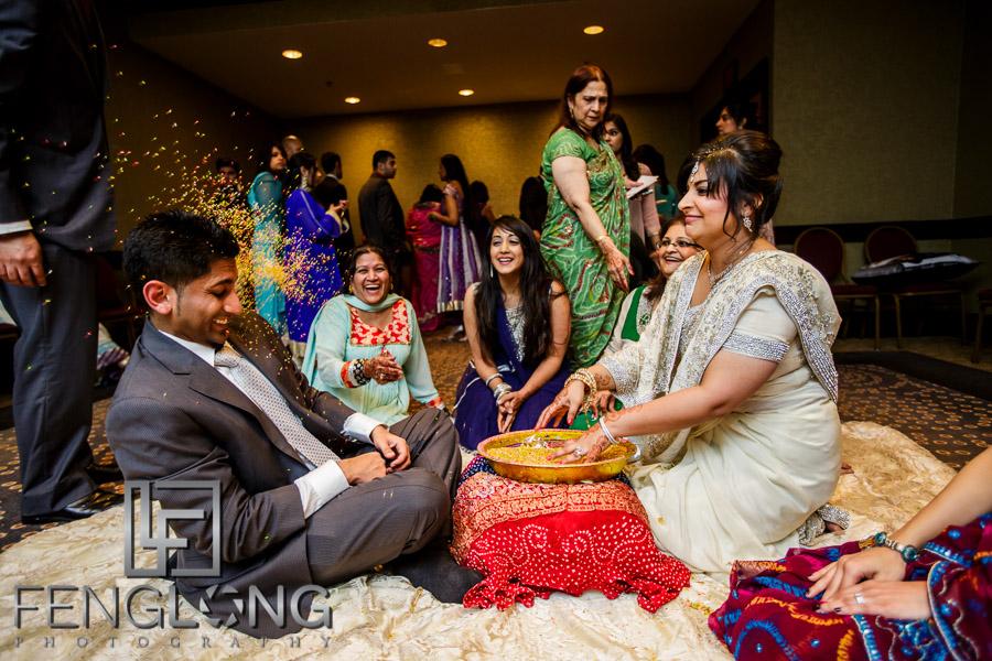 Ismaili Muslim Indian bride throwing rice during Khoba Khobi ceremony