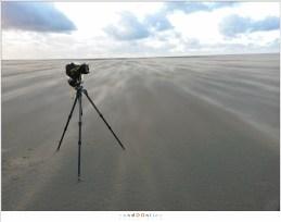 Het zand jaagt over het strand