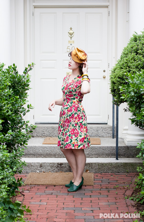 A bold 1940s floral dress paired with a yellow tilt hat, green shoes, and a stack of Bakelite bangles