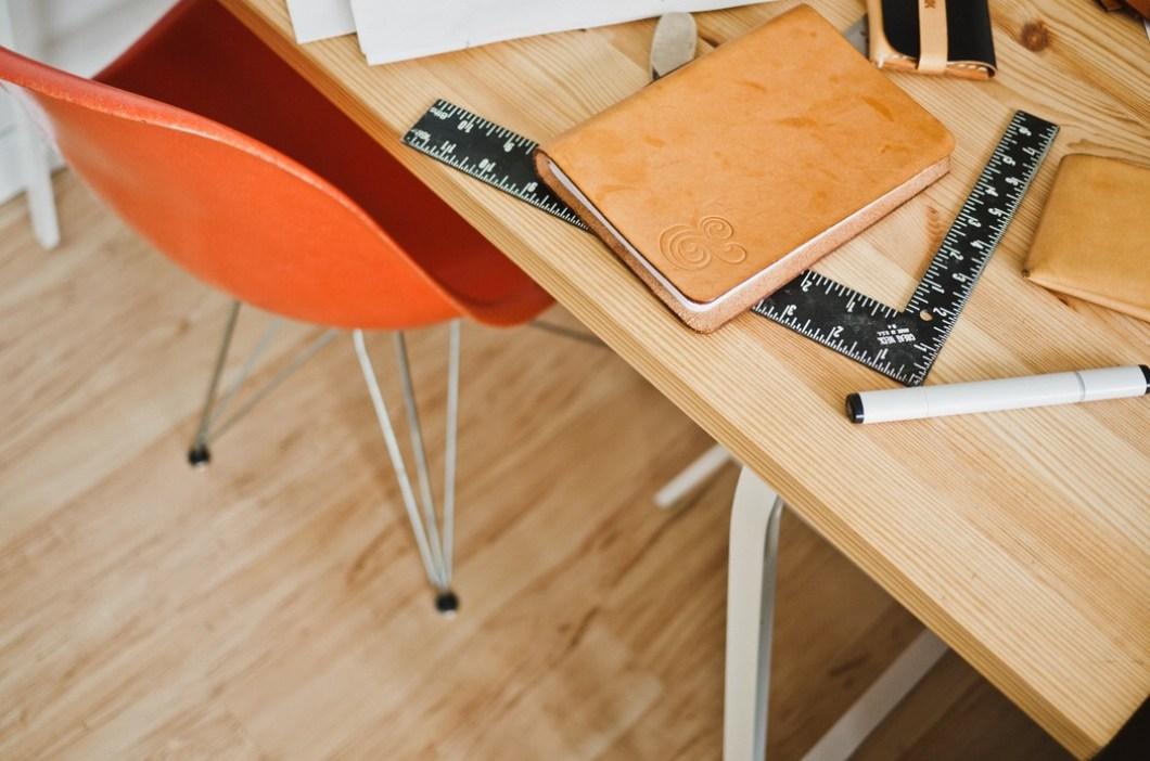 Foto gratis de una mesa de escritorio con regla, libreta y rotulador