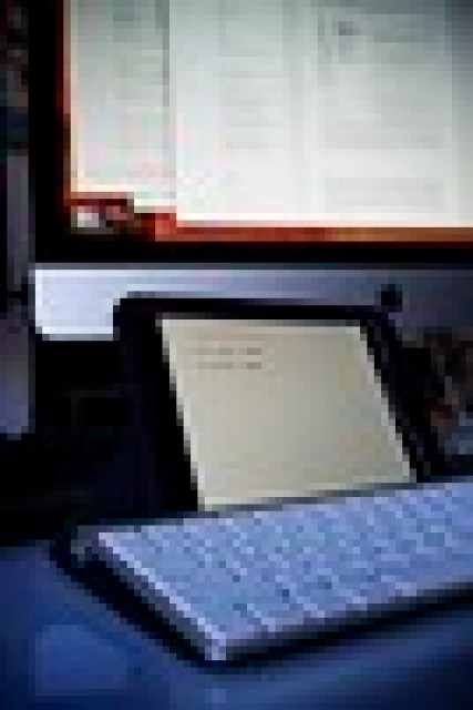 Photo showing an iPad with a Apple Wireless Keyboard editing Ulysses for iPad while the background shows an iMac editing Ulysses for Mac.