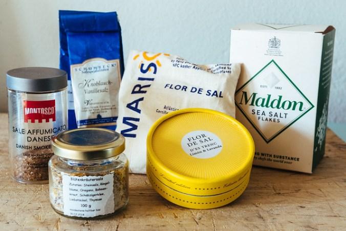 Zalig zout, vlnr: gerookt zout, kruidenzout, vanillezout, grof Portugees zeezout, zeezout met citroen en lavendel uit Mallorca en Maldon zoutvlokken