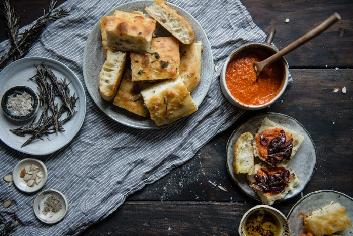 herbed focaccia with caramelized onions & romesco   two red bowls