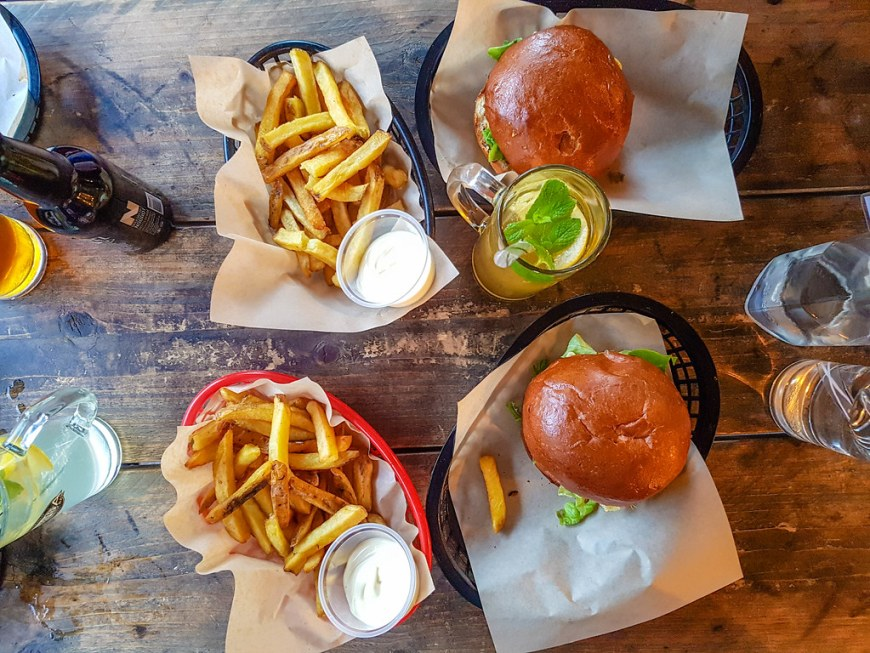 A photo of burgers and fries taken from above the table