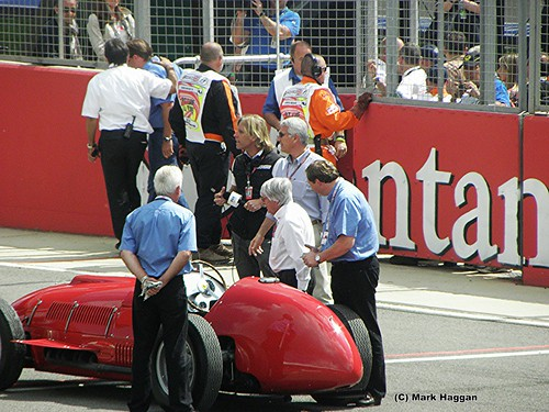 Bernie Ecclestone watches Fernando Alonso drive a historic Ferrari at the 2011 British Grand Prix