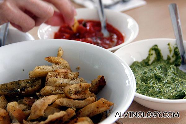 Crispy pita sticks with three different dips - green chili, fresh tomato and a third yellow sauce