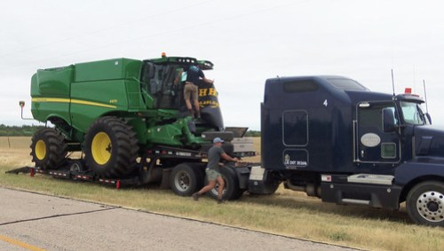 Oak removes the windshield guard while Montana works on helping to get ready to unload the combine