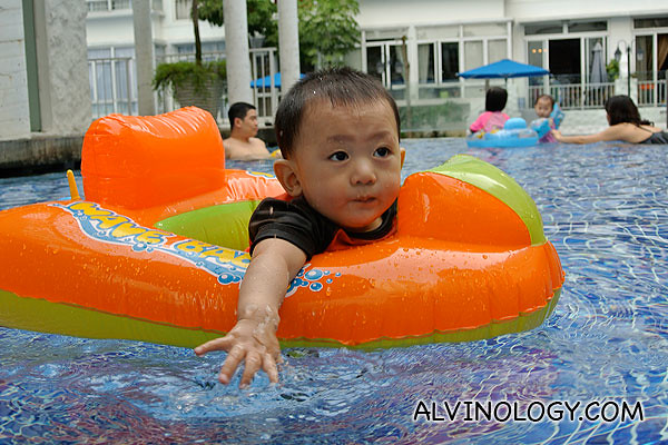 Asher paddling on his own in a float