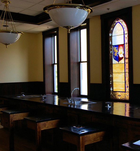 shows long back counter with sinks.  From the right side blacktop desks protrude.  There  are  gas ports at the desks and counter tops.  The room has walnut wainscoting and features a large class stain glass window.