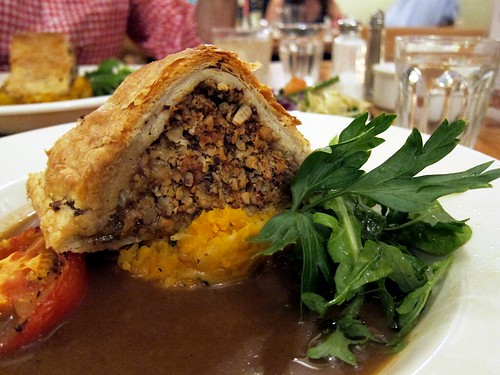 A tall phyllo crust stuffed with ground nuts and lentils sitting on a sweet potato mash and surrounded by a pool of dark brown gravy.