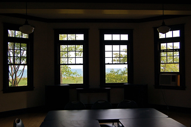 view of Lake Michigan's blue water across a green lawn through large bay window
