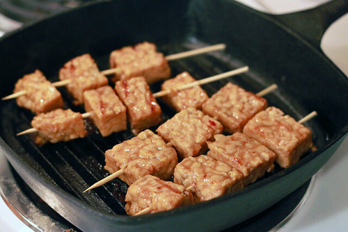 Cast-iron grill pan sitting on an electric stove. In it are four wooden skewers with squares of tempeh on them.