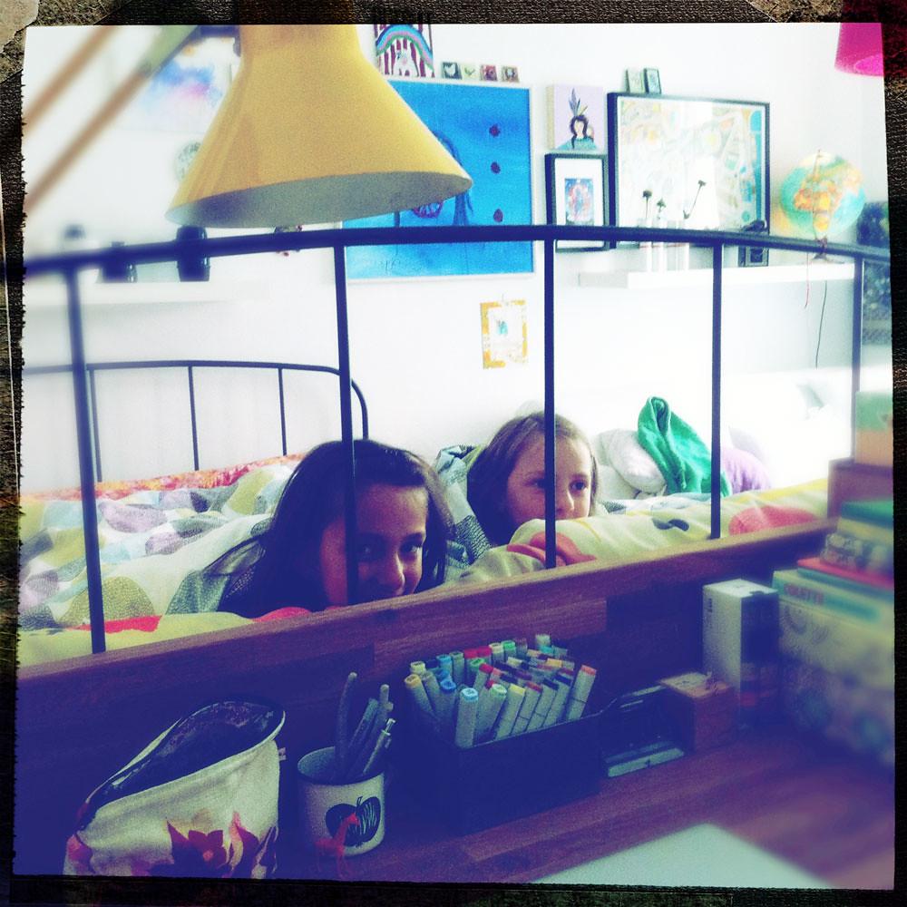 The girls playing peekaboo in bed