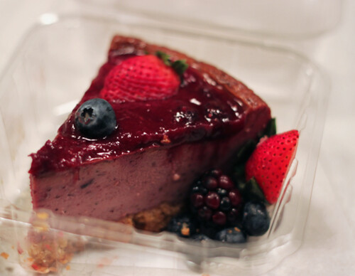 Three-quarter view of a rich purple cheesecake topped with blackberries, strawberries, and blueberries.