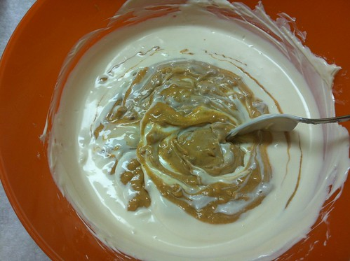 Stirring peanut butter into the melted white chocolate.
