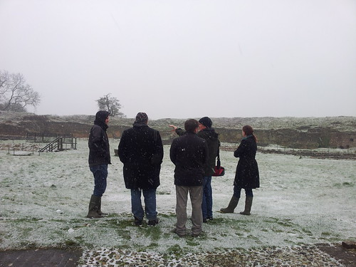 Five people stand with their backs to the camera in the centre of the standing remains of the Old House at Basing House. They are all wearing coats with hoods up and it is snowing gently. The landscape around them is covered in snow. One person is pointing towards the archaeological remains.