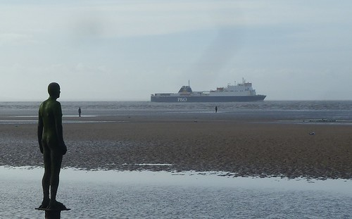 Antony Gormley fugure looking out to sea as a ferry boat goes past.
