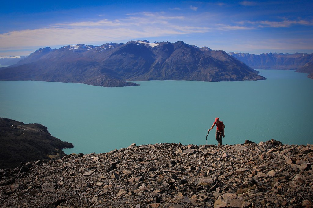 An exploration hike up an unnamed peak, raising high above the Eastern arm of the Lago O'Higgins, Aysen, Patagonia, Chile. Remark the Chilea border post of Candelario Mancilla down left.