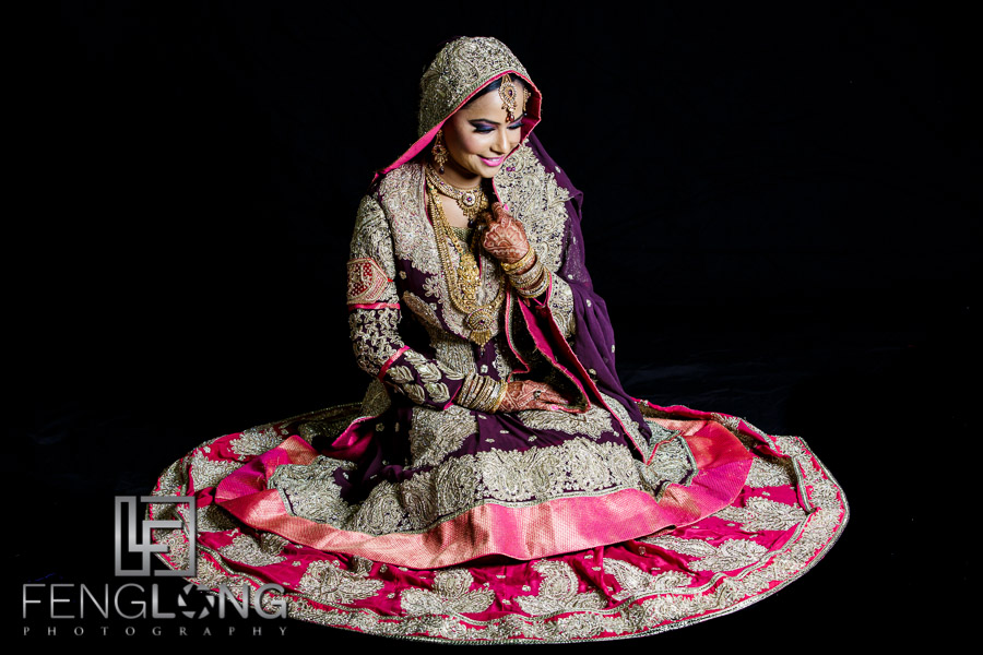 Indian bride in wedding gown on black background
