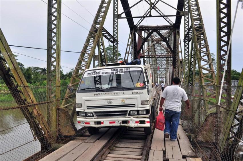 Puente que une Costa Rica con Panamá sobre un Río y por el que circulan personas, caminiones y algún que otro tren, el suelo es de tablones de madera con huecos donde se ve el río. Bocas del Toro, escondido destino vírgen en Panamá - 7598165400 2a61ccf08a o - Bocas del Toro, escondido destino vírgen en Panamá