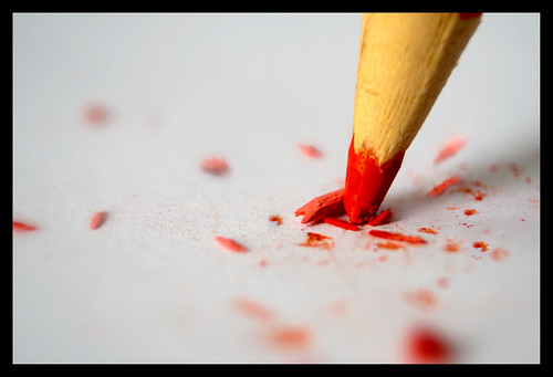 A red pencil tip breaking on a white surface