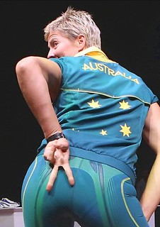 women in Australian beach volleyball uniform - tigh cycling-type shorts with a loose sleeveless tracksuit top. She is posed, bum pushed at the camera, with her fingers making an upside down V sign over her buttocks.