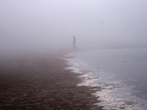 man walking the foggy shoreline at Stroomi beach, Tallinn, Estonia