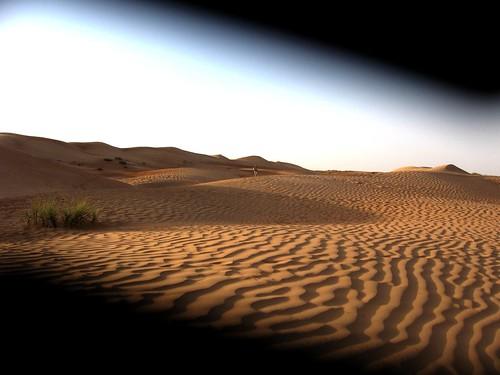 Desert sand ripples through a trapped camera lens