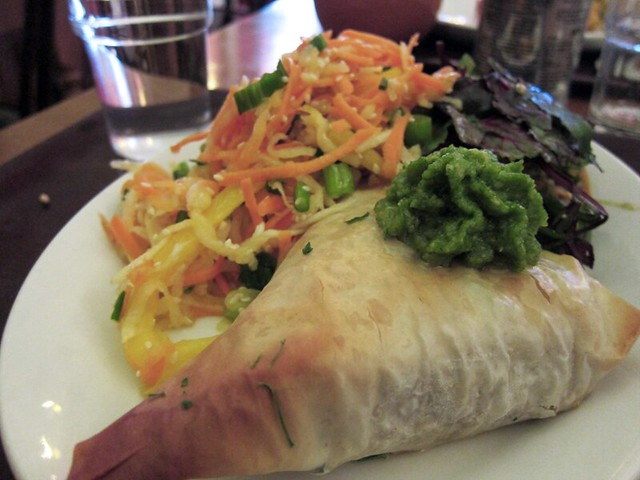In the foreground is a large triangular phyllo dough packet, stuffed quite full. In the background is a raw cabbage and carrot slaw and a green salad.