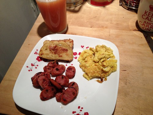 Photo of Sunday brunch meal including pretzel roll french toast, seasoned parmesan eggs, apple-gouda sausage and grapefruit juice.